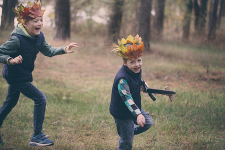 sibling rivalry: Two Brothers running in a forest on autumn day. Boys have a crown from leaves on the head and swords in hands.
