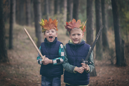 Two Brothers cuddling  in a forest on autumn day. Little kids hugging.