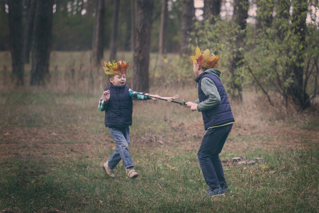 sibling rivalry: The boys portrait with a crown on the head and a sword in hands. The thoughtful boy dreams Stock Photo