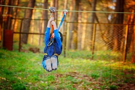 Little happy child boy in adventure park in safety equipment in summer day Standard-Bild