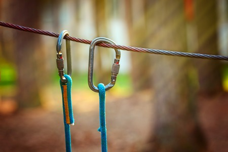 hasp: Climbing Sports Image Of A Carabiner On A Metal Rope In A Forest. Stock Photo