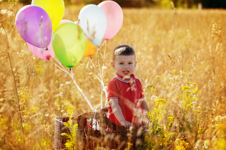 yelow: Sweet little boy portrait in a basket with colorful ballons in yelow field Stock Photo