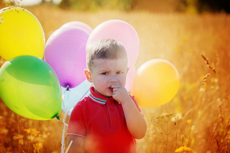 ballons: Portrait boy with colorful ballons on yellow field