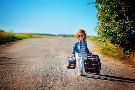 happy and joyful child with suitcases. vacation and trip concept.summer time Standard-Bild