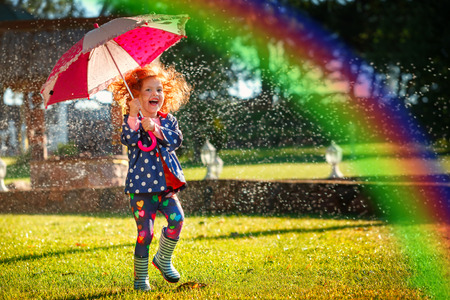 Laughing girl in the rain under umbrela with a rainbow. Standard-Bild
