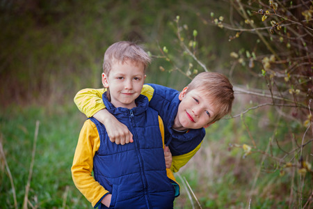sibling: Portrait Two little sibling boys hugging and having fun outdoors n the warm spring day. Stock Photo