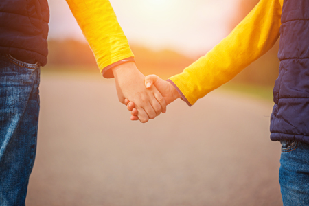 holding hands while walking: Closeup of children holding hands while walking in park on the sunset. Stock Photo