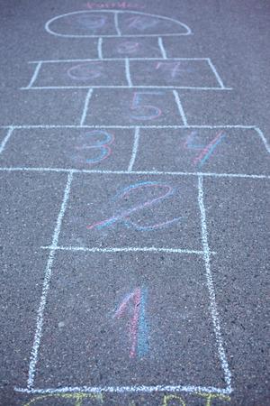 carves: Hopscotch drawn on asphalt. Soft focus on number 1. Stock Photo