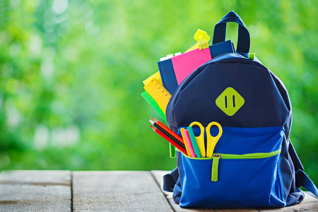blue pen: Full School backpack on wooden and nature background Stock Photo