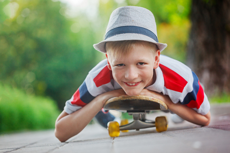 skate park: Closeup portrait smiling boy in hat  lying on skateboard in summer day. Stock Photo