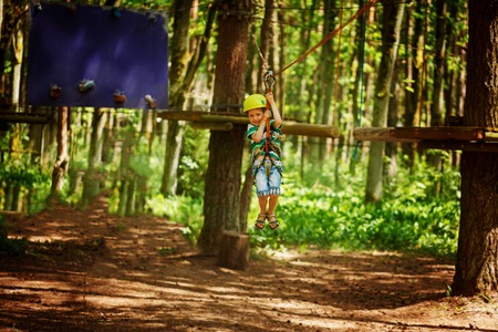 Adventure climbing high wire park - little child on course in mountain helmet and safety equipment. Stock Photo