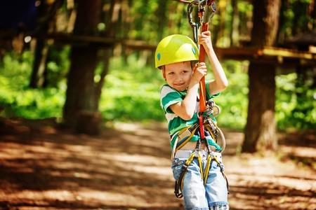 Adventure climbing high wire park - little child on course in mountain helmet and safety equipment. Standard-Bild