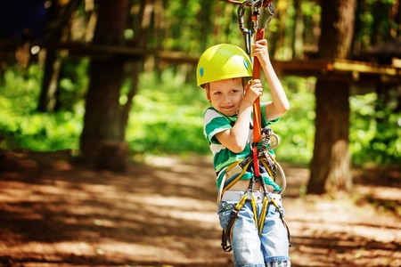 Adventure climbing high wire park - little child on course in mountain helmet and safety equipment. Reklamní fotografie