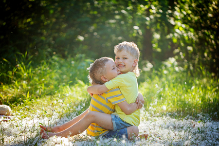 comrades: Two little boys friends hug each other in summer  garden. Brother love. Concept friendship Stock Photo