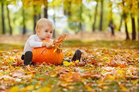 秋の庭の草の上に座って手でカボチャの大きなオレンジ色の小さな男の子 写真素材