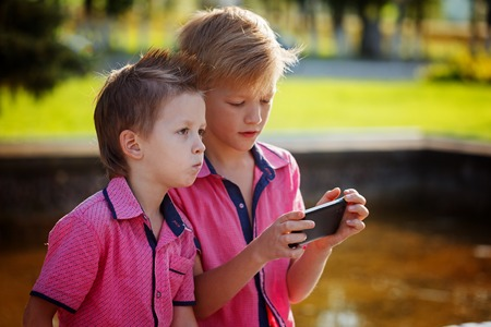Two little boys playing games on mobile phone in sunny day Stock Photo