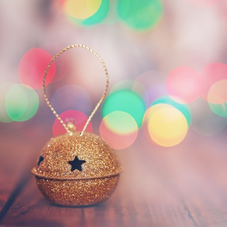 jingle bell: Gold Metal Jingle Bell with star on Wooden Table with copy space, selective focus. Christmas background with colorful boke Stock Photo