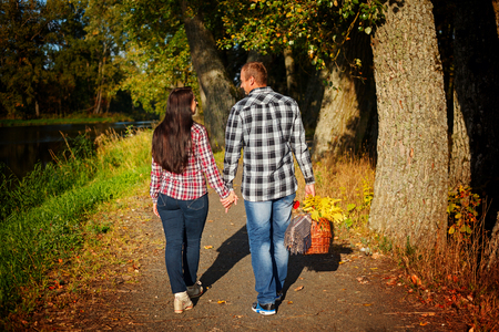 go for: Man and woman  go for walk on autumn picnic. Couple walking in autumn forest