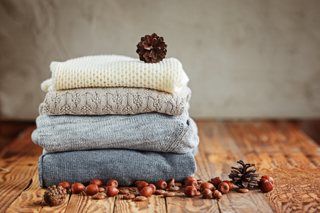 Pile of knitted winter clothes on wooden background, sweaters, space for text