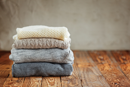 Stapel van gebreide winter kleding op houten achtergrond, sweaters, ruimte voor tekst Stockfoto