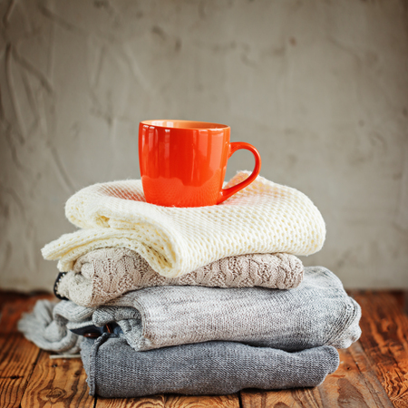 Sweaters Closeup, Stack of knitted winter clothes with red cup on wooden background Standard-Bild