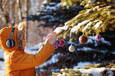 Cute boy in warm cloth and hat catching christmas ball in winter park. Kids play outdoor in snowy forest. Children catch christmas balls