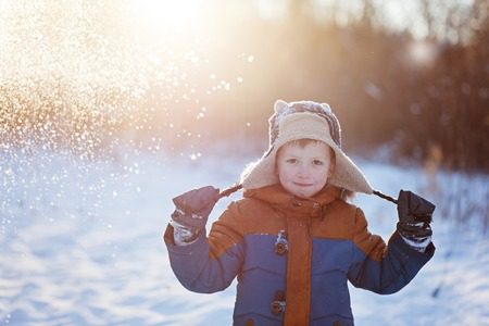 outoors: Winter little child playing throws up snow outdoors during snowfall. Active outoors leisure with children in winter on cold snowy days.