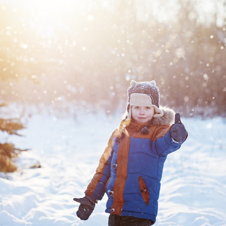 outoors: Happy little child playing throws up snow outdoors during snowfall. Active outoors leisure with children in winter on cold snowy days.