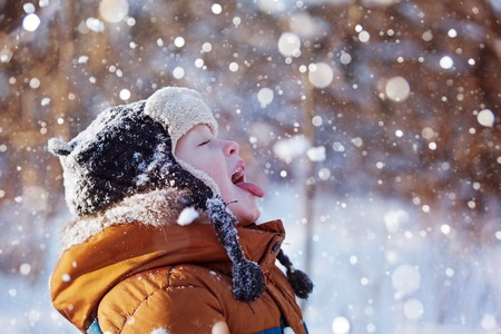 caching: Portrait of a cute little boy in warm clothes who catches snowflakes mouth in winter sunny day