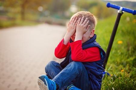 Kleine jongen huilen, viel van de scooter in de open lucht. Stockfoto