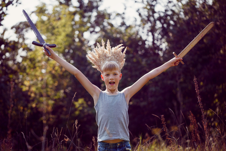 Portrait Boy with a crown on the head and a sword in hands in sunny summer day. Succes concept. Banque d'images