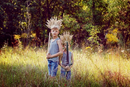 Portrait Two Brothers have a crown from dry grass on the head and swords in hands. Joy and play concept. Stock Photo
