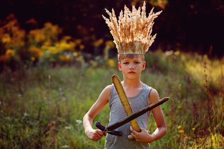 Portrait Boy with a crown on the head and a sword in hands in sunny summer day.