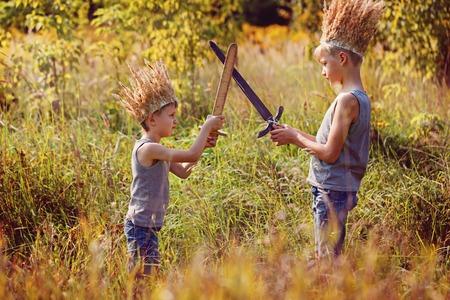 niños actuando: Dos hermanos tienen una corona de hierba seca en la cabeza y las espadas en las manos. La alegría y el juego concepto Foto de archivo