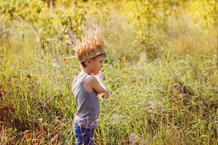 Little boy have a crown from dry grass on the head and swords in hands. Stock Photo