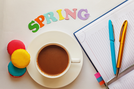 Top view image of spring word, open blank notebook and colourful macaroons and cup of tea or coffee