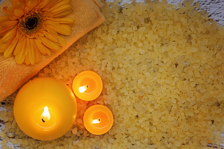 fire flower: Spa yellow products setting. Sea salt ,towel and candles on dark wooden background
