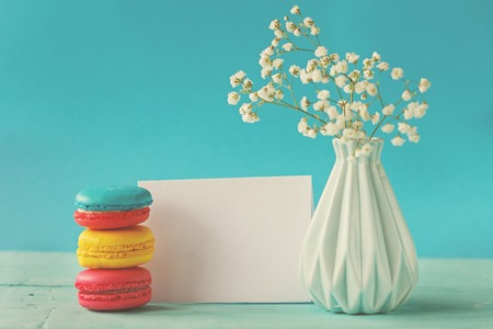 Blank paper card with cup of tea andvase in flower and macaroons for woman day