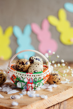 Easter composition of Easter quail eggs in the basket and with bunny garland on wooden background. Holiday concept with copy space.
