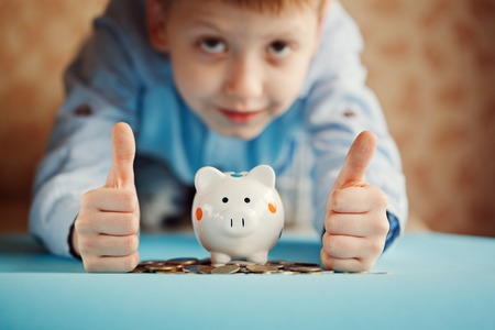 Hands kid thumbs up and piggy bank or money box