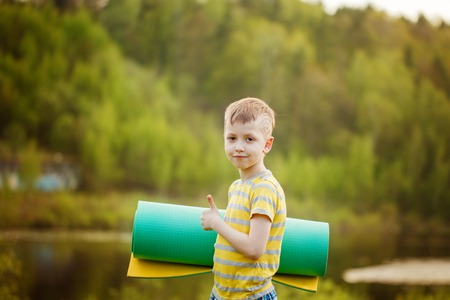Cute boy doing sports on nature background. Sporty little boy doing exercises in the summer park. Lifestyle and sport concept.