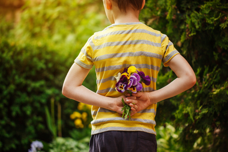 Child hands holding a bouquet pansies flower . Focus for flowers. Back view.