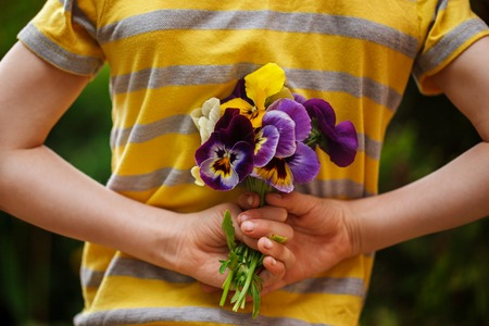 arm bouquet: Child hands holding a bouquet pansies flower . Focus for flowers. Back view.