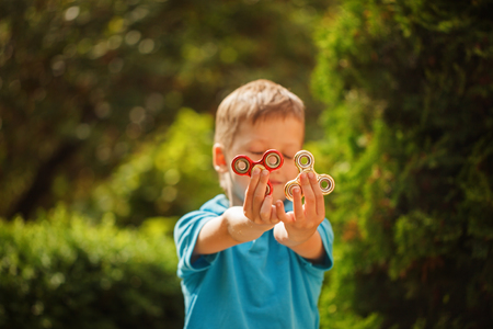 Cute little boy playing with fidget hand spinners in summer day. Popular and trendy toy for children and adult