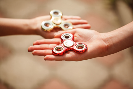 Children hands holding fidgqet hand spinners. Trendy and popular toy for children and adult Stock Photo