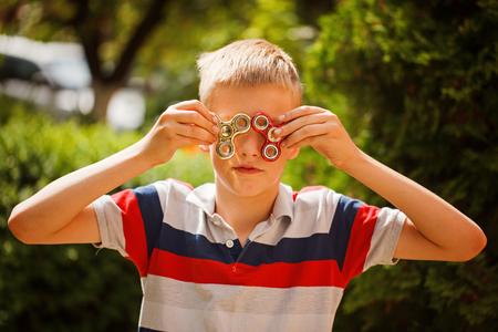 Schoolboy playing with fidget hand spinners in summer day. Popular and trendy toy for children and adult