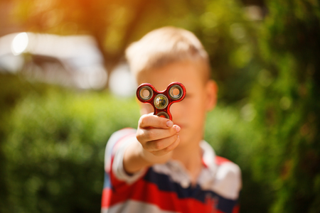 Schoolboy holds a spinner fidget in his hands. Trendy and popular toy for children and adult