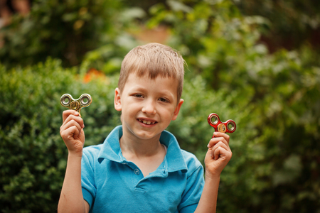 Cute little boy playing with fidget hand spinner in summer day. Popular and trendy toy for children and adult