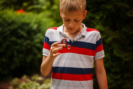 Yong boy holds a spinner fidget in his hands. Trendy and popular toy for children and adult