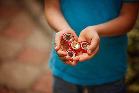 Cute little boy holds a spinner fidget in his hands. Trendy and popular toy for children and adult Stock Photo